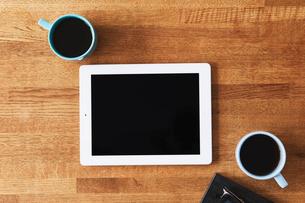 木のテーブルとスマートフォンとコーヒーの写真素材 [FYI01604741]