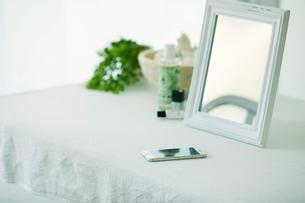 鏡と机と化粧品とスマートフォンの写真素材 [FYI01604745]