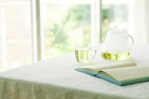 テーブルに置かれたティーポットとカップと本の写真素材 [FYI01604767]