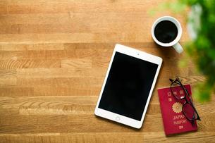 テーブルに置かれたコーヒーとタブレットPCとパスポートの写真素材 [FYI01604779]