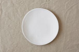 ベージュの麻の布と白い皿の写真素材 [FYI01604819]