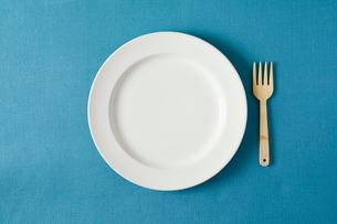 青のテーブルクロスと白い皿とフォークの写真素材 [FYI01604833]