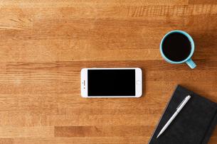 木のテーブルとスマートフォンとコーヒーの写真素材 [FYI01604878]