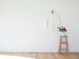 壁にかかった白いシャツとスツールの写真素材 [FYI01605007]