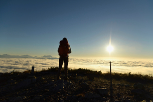 雲海と日の出を見る登山者の写真素材 [FYI01605110]