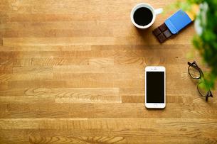 テーブルに置かれたスマートフォンとコーヒーの写真素材 [FYI01605169]