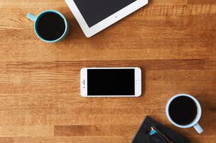 木のテーブルとスマートフォンとコーヒーの写真素材 [FYI01605187]