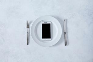 白とグレーで塗装された背景と白い皿とカトラリーとスマートフォンの写真素材 [FYI01605471]