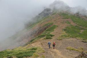 霧に包まれた登山道を登る登山者の写真素材 [FYI01605563]