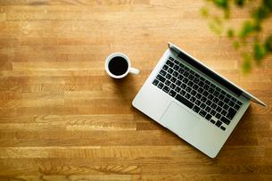 テーブルに置かれたノートパソコンとコーヒーの写真素材 [FYI01605615]
