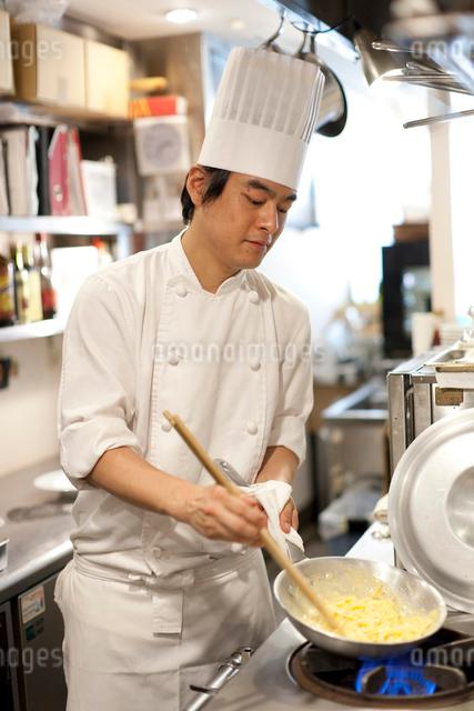 レストラン厨房でシェフがフライパンを振り料理を作るの写真素材 [FYI01605642]