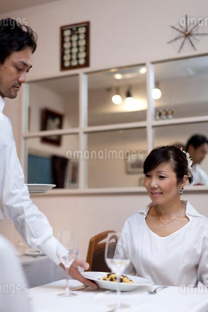 レストランで料理をサービスする人とテーブルの客の写真素材 [FYI01605667]