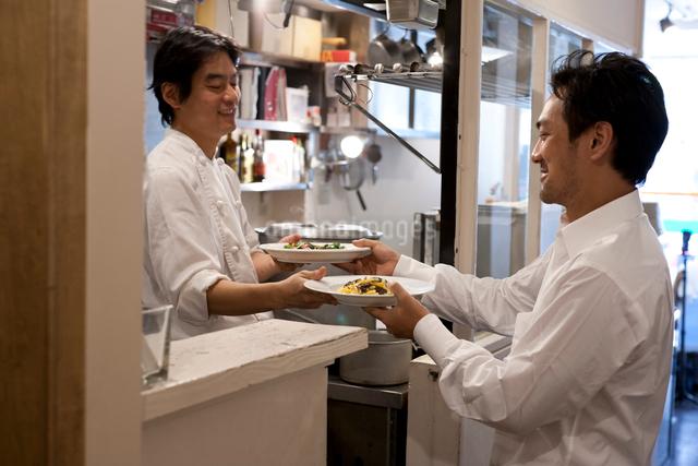 レストラン厨房で料理を渡すシェフと受け取るギャルソンの写真素材 [FYI01605722]