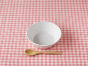 ピンクのチェックの布と白い皿と木のスプーンの写真素材 [FYI01605776]