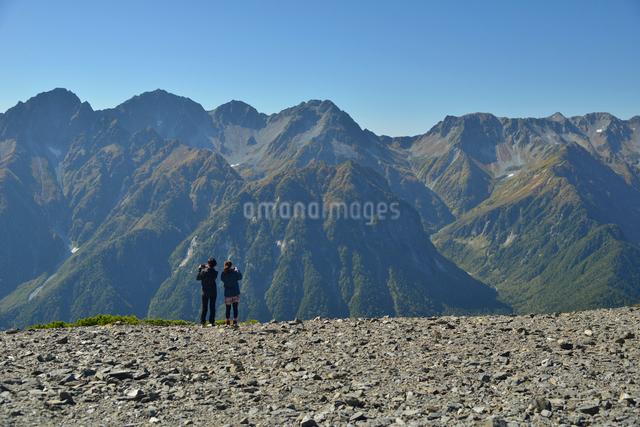 穂高連峰と撮影をしている山ガールの写真素材 [FYI01605784]
