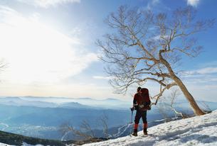 残雪の登山道で景色を眺めている登山者の写真素材 [FYI01605795]