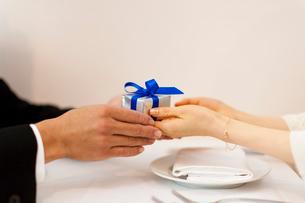 レストランで指輪を持ちプロポーズする男性と女性の添えた手の写真素材 [FYI01605838]