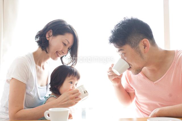 ダイニングでコーヒーを飲むお父さんの真似をする子どもと笑顔のお母さんの写真素材 [FYI01605911]