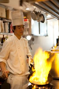 鍋にブランデーを注ぎフランベの炎をあげるシェフの写真素材 [FYI01605934]