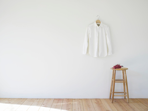 壁にかかった白いシャツとスツールの写真素材 [FYI01605969]