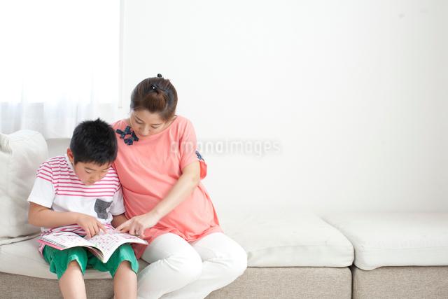 ソファーに座って一緒に雑誌を見て会話する妊婦のお母さんと小学生の子供の写真素材 [FYI01605982]