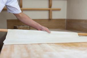 そば生地を麺棒で伸ばす職人の写真素材 [FYI01606005]