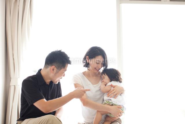 リビングで赤ちゃんを抱っこするお母さんの隣で笑顔であやすお父さんの写真素材 [FYI01606062]