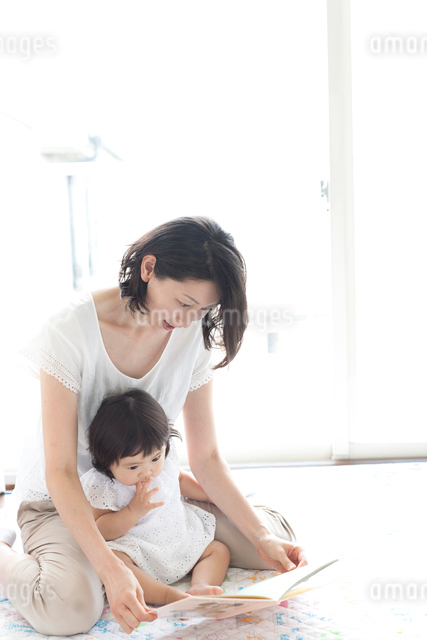 リビングで赤ちゃんを抱っこしながら絵本を読んであげる笑顔のお母さんの写真素材 [FYI01606086]
