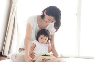 リビングで赤ちゃんを抱っこしながら絵本を読んであげる笑顔のお母さんの写真素材 [FYI01606092]