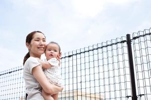 フェンスのある場所で赤ちゃんを抱っこしたお母さんが青空を見上げながら気持ちよさそうに微笑むの写真素材 [FYI01606106]