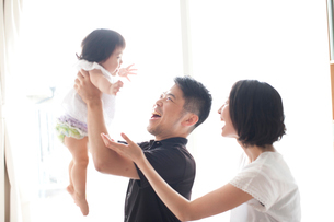 リビングでお父さんが赤ちゃんを抱っこし遊ぶ隣で笑顔で一緒にあやすお母さんの写真素材 [FYI01606107]