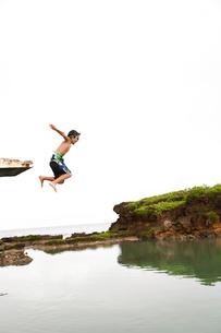 高台から両手を広げて海に飛び込んだ瞬間の男の子の写真素材 [FYI01606110]
