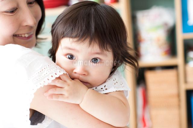 笑顔のお母さんに抱っこされ涙をためて甘える指しゃぶりしている赤ちゃんの写真素材 [FYI01606171]