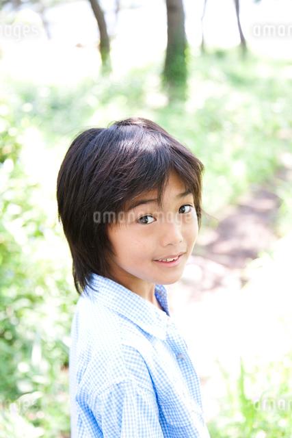 野原で散歩しながら振り返って笑う男の子の写真素材 [FYI01606179]