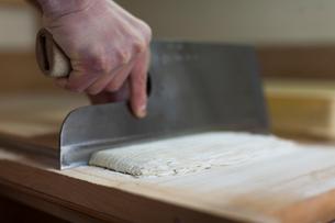 そば生地を包丁で切る職人の手の写真素材 [FYI01606283]