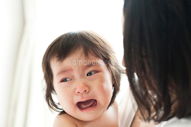 お母さんに抱っこされて泣いている赤ちゃんの写真素材 [FYI01606333]