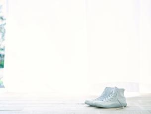 部屋に置かれた白いスニーカーの写真素材 [FYI01606378]