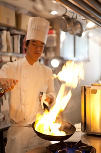 鍋にブランデーを注ぎフランベの炎をあげるシェフの写真素材 [FYI01606438]