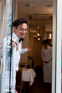 レストランでドアを開け客を笑顔で招き入れるウエイターの写真素材 [FYI01606469]