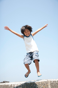 海のそばの防波堤でジャンプして遊ぶ笑顔の男の子の写真素材 [FYI01606481]