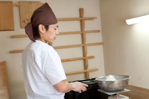 そば粉の量を測る料理人の横顔の写真素材 [FYI01606484]