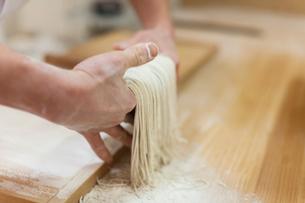 そばを切る作業をしている料理人の手の写真素材 [FYI01606511]