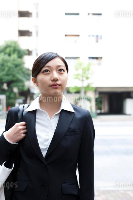 スーツを着てビジネスバッグを持って空を見上げる女性の写真素材 [FYI01606563]