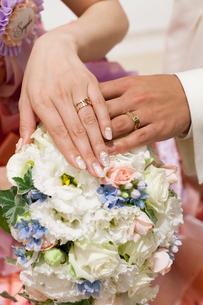 結婚式でブーケに手を添える結婚指輪をはめた新郎新婦の写真素材 [FYI01606621]