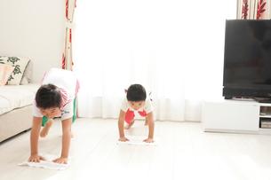 並んでリビングの床の雑巾がけの手伝いをする楽しそうな小学生の兄弟の写真素材 [FYI01606944]