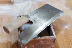 木のまな板の上にそばを切るための包丁と道具のマスの写真素材 [FYI01606961]