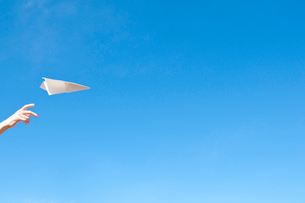紙飛行機を飛ばす女の子の手の写真素材 [FYI01606975]