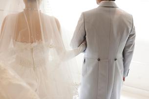 結婚式で腕を組み歩く新郎新婦の後ろ姿の写真素材 [FYI01607272]