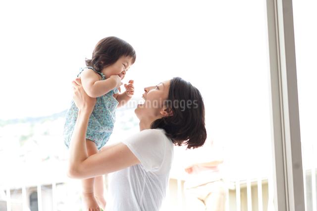 お母さんに抱っこされ高く持ち上げられて笑って喜ぶ赤ちゃんの写真素材 [FYI01607860]
