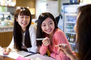 カフェで楽しそうにプライベートレッスンを受ける笑顔の女性ふたりの写真素材 [FYI01607931]